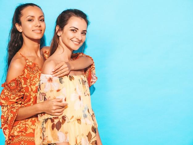 Sexy zorgeloze vrouwen poseren in de buurt van blauwe muur. plezier en knuffelen. modellen tonen een goede relatie. vrouw zonder make-up