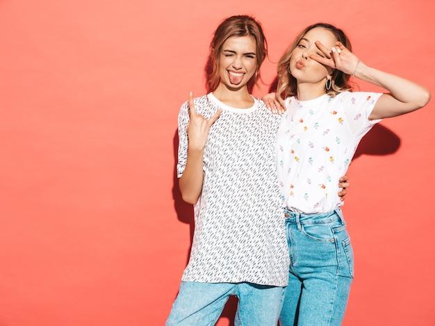 Sexy zorgeloze vrouwen poseren in de buurt van roze muur. ze tonen vrede en rock and roll teken
