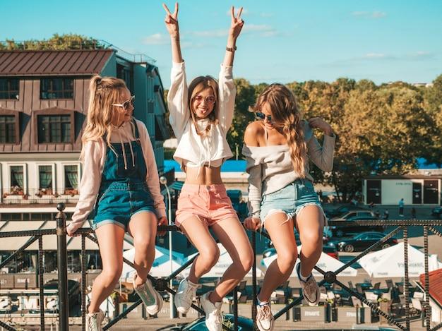 Sexy zorgeloze vrouwen zitten op leuning de straat ze verhogen handen
