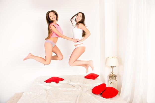 Sexy zussen in pyjama's springen op het bed en hand in hand