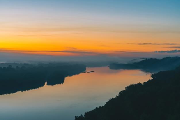 Sfeervol landschap met weerspiegeling van gouden dageraad in rivier
