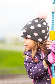 Sfeervol livestyleportret van een klein grappig meisje in een warme jas