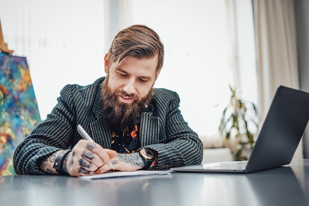 Sfeervol portret van een volwassen computerprogrammeur met tatoeages en stijlvolle kleding. vrolijke man doet zijn papierwerk aan tafel.
