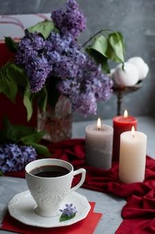 Sfeervolle foto: zwarte koffie en een wit kopje, een boeket seringen, een paar grote kaarsen, marshmallows op een grijs oppervlak