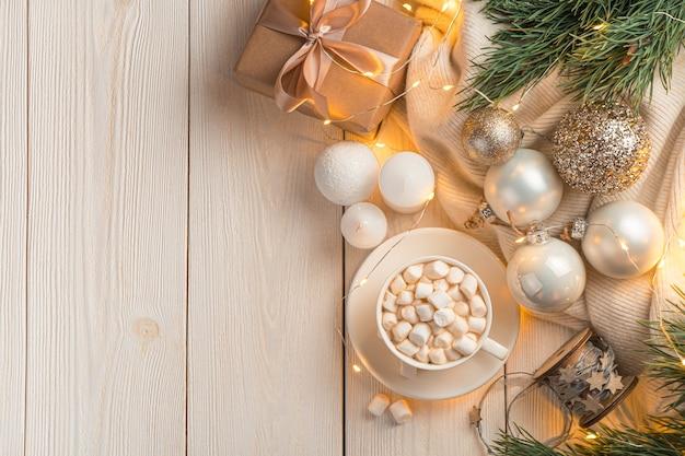Sfeervolle kerstachtergrond met een kopje koffie en kerstversiering op een lichte achtergrond in het licht van brandende lichten. bovenaanzicht, kopieer ruimte.