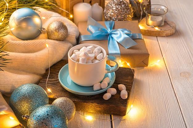 Sfeervolle kerstachtergrond met een kopje koffie kerstversieringen en een cadeau