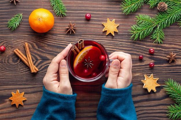 Sfeervolle kerstavond met een kopje rode thee of glühwein in vrouwenhanden