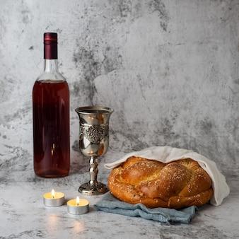 Shabbat shalom - challahbrood, shabbatwijn en kaarsen op grijs.