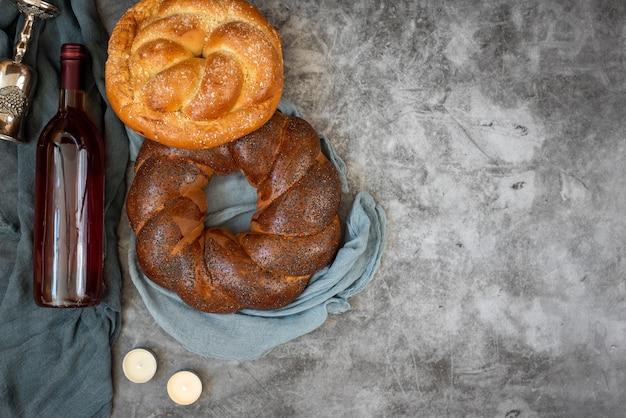 Shabbat shalom - challahbrood, shabbatwijn en kaarsen op grijze achtergrond. bovenaanzicht. met kopie ruimte