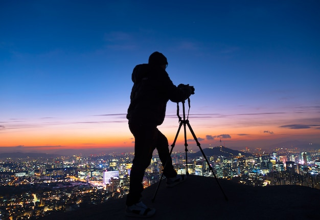 Shadow man standing silhouette op achtergrond van sunrise sky en fotograaf met een camera gemonteerd op statief in seoul zuid-korea