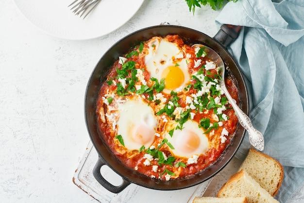 Shakshouka, gepocheerde eieren in tomatensaus, olijfolie.