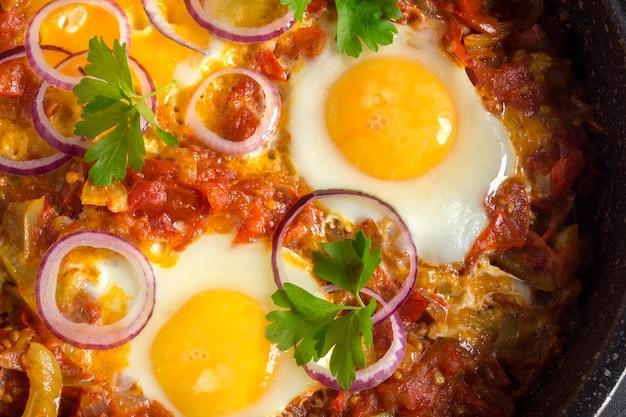Shakshuka, een traditioneel israëlisch gerecht. sunny side up ei met gestoofde tomaten.