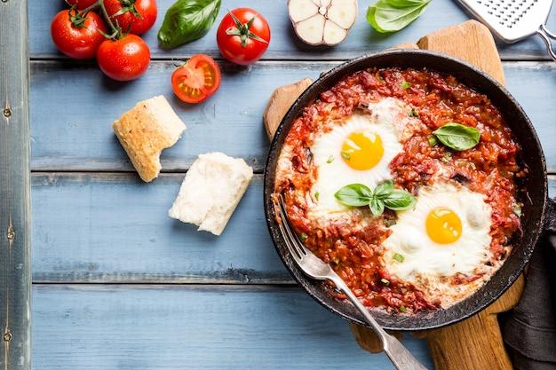 Shakshuka, gebakken eieren in tomatensaus in ijzeren koekenpan. typisch israëlisch eten. bovenaanzicht.