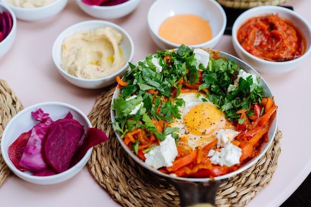 Shakshuka, gebakken eieren in tomatensaus op tafel