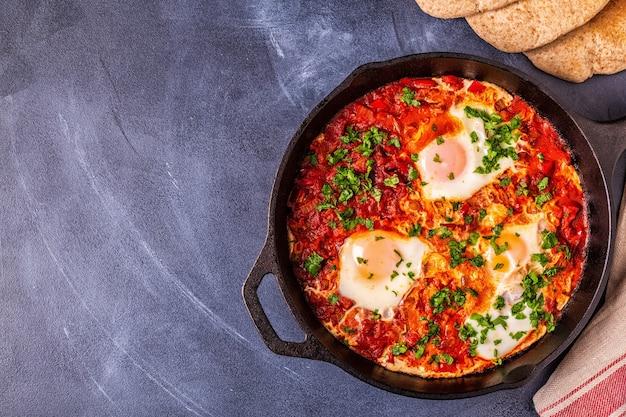Shakshuka in een koekenpan eieren gepocheerd in pittige tomaten-pepersaus