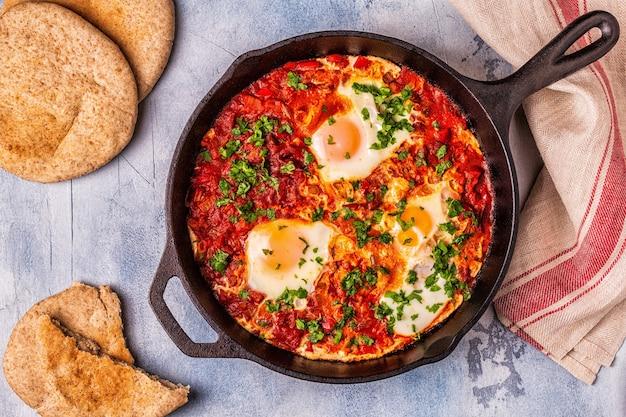 Shakshuka in een koekenpan. eieren gepocheerd in pittige tomaten-pepersaus.