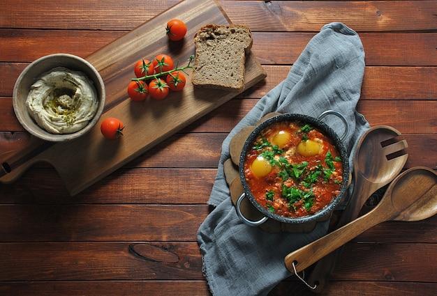 Shakshuka in pan met humus op een bruin houten tafel