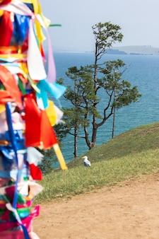 Shaman's pilaar tegen de achtergrond van een zeemeeuw en een boom en het baikalmeer. 13 pijlers op kaap burkhan, olkhon-eiland.