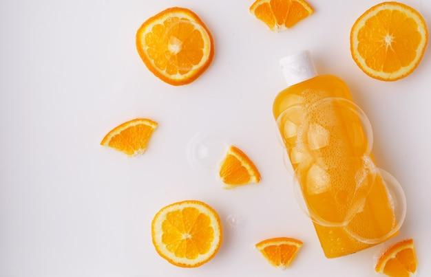 Shampoo, douchegel, oranje vloeibare zeep met natuurlijke ingrediënten in een transparante fles op een lichte achtergrond met bubbels en stukjes sinaasappel