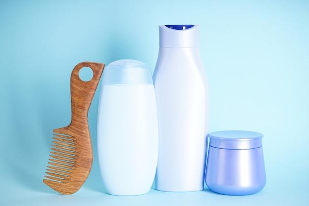 Shampoo, fles conditioner en houten haarborstel op blauwe achtergrond
