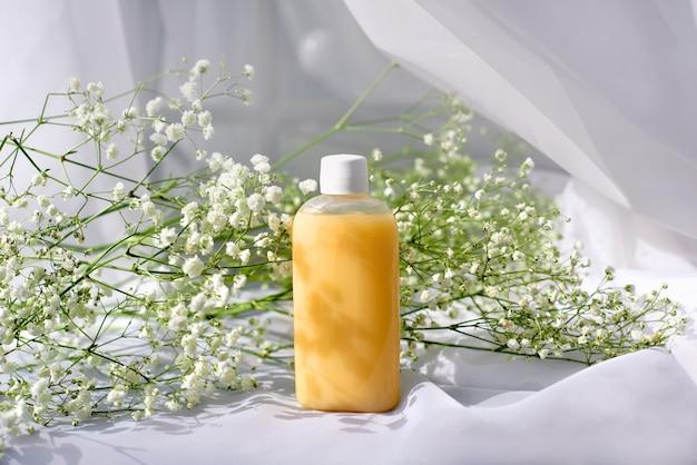 Shampoo, gel of lotion op doorzichtige plastic fles met deksel op witte achtergrond met lentebloemen