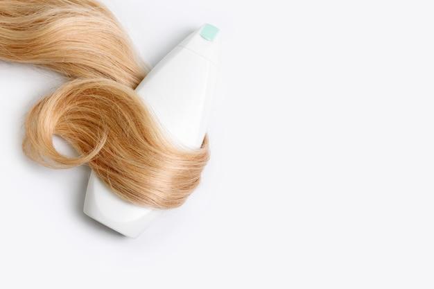 Shampoo of conditioner fles verpakt in lok van krullend blond haar geïsoleerd op een lichte achtergrond, bovenaanzicht. plat leggen, ruimte voor tekst kopiëren. haarverzorgingscosmetica, schoonheidsproducten voor haarverzorging, haarbehandeling.