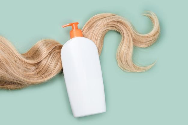 Shampoo- of conditionerfles verpakt in krullend blond haar op lichte mintachtergrond, bovenaanzicht. plat lag in pastelkleuren, mockup. haarverzorgingscosmetica, schoonheidsproducten voor haarverzorging, haarbehandeling