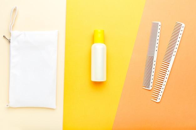 Shampoo oranje fles met kammen en make-up tas. schoonheidsdiensten, cosmetica voor haarbehandeling. kapper tools haar cosmetica toiletartikelen. bovenaanzicht gele achtergrond.