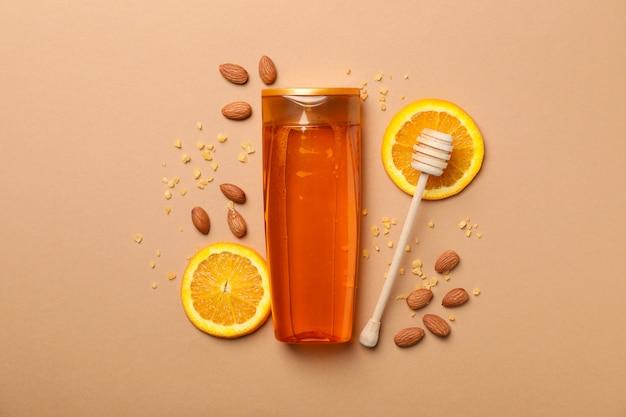Shampoofles en natuurlijke ingrediënten op ambachtelijke achtergrond. lege ruimte op fles