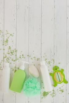 Shampooflessen op houten backround. accessoires voor babybadjes. spullen voor kinderen. badkamerbuizen, balsem, zeezout, zeep.