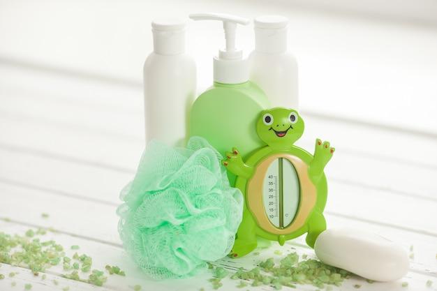 Shampooflessen op houten tafel. accessoires voor babybadjes. spullen voor kinderen. badkamerbuizen, balsem, zeezout, zeep.