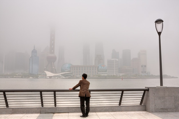 Shanghai, china luchtvervuiling, hoogbouw gehuld in zware smog, lucht in de stad bleef ernstig vervuild, man stond op de bund en kijkt naar het pudong-district.