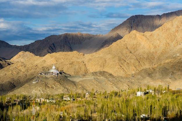 Shanti stupa met de grote berg op achtergrond en leh-stad met de gouden leafin herfst