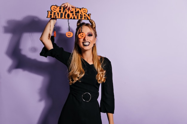 Shapely gelukkig meisje lachend in halloween. indoor foto van prachtig wit vrouwelijk model in zwarte jurk geïsoleerd op pastel muur.