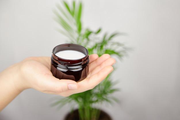 Shea butter moisturizer voor huid- en haarverzorging. hand met natuurlijke organische cosmetische crème in pot.