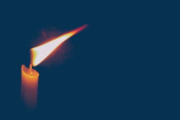 Shedding light kaars op donkere achtergrond vertegenwoordigen religie aanbidding geloof