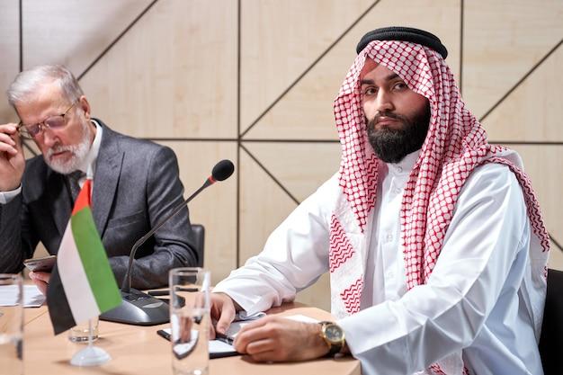 Sheikh man presenteert zijn ideeën aan collega's en luistert naar ideeën voor succesinvesteringen in lichte, moderne kantoorruimte, zit achter de microfoon en kijkt naar de camera