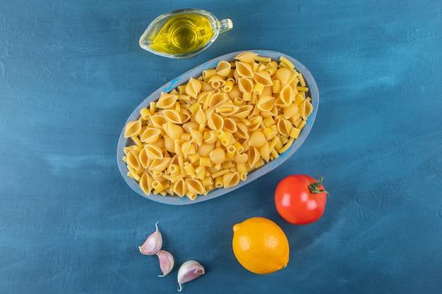 Shell ongekookte pasta in een bord met verse rode tomaat en knoflook.