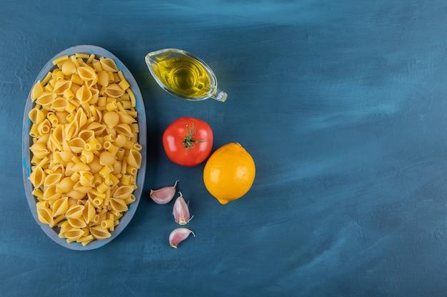 Shell ongekookte pasta in een bord op een donkerblauwe achtergrond.