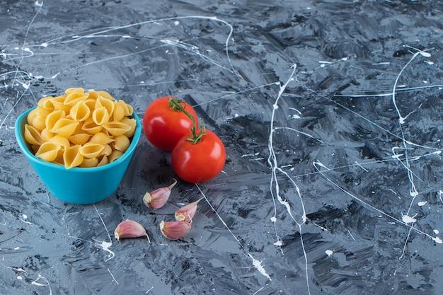 Shell ongekookte pasta in een kom met verse rode tomaten en knoflook.