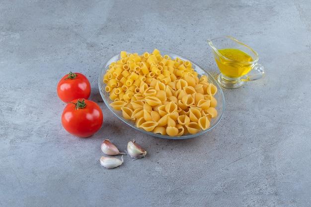 Shell ongekookte pasta met rauwe droge ditali rigati in een glazen kom.