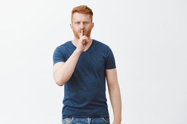 Shh, ik heb stilte nodig. portret van knappe ernstig uitziende en strenge man met rood haar en borstelharen, fronsend, zwijgzaam gebaar maken met wijsvinger over mond, vragen stil houden