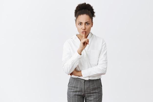 Shh niet storen, we hebben hier een afspraak. geërgerd boos en streng vrouwelijke ondernemer in wit overhemd en broek, fronsend en zwijgend zeggen, wijsvinger voor mond houden, stilte eisen in de klas