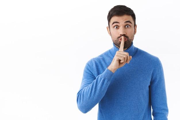 Shhh hou je stem laag. enthousiaste knappe blanke man bereidt verrassing voor, vraagt stil te zijn, zwijgt met wijsvinger tegen de lippen gedrukt, heeft stilte nodig, staande witte muur
