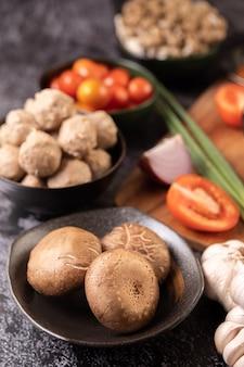 Shiitake-paddenstoelen met knoflook, tomaat, paprika, bosui en rode ui op een zwarte cementvloer.