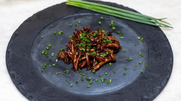 Shimeji-paddenstoel die met bieslook op zwarte steenplaat wordt gediend. typische oosterse maaltijd. detail van voedselschotel, close-up, selectieve nadruk.