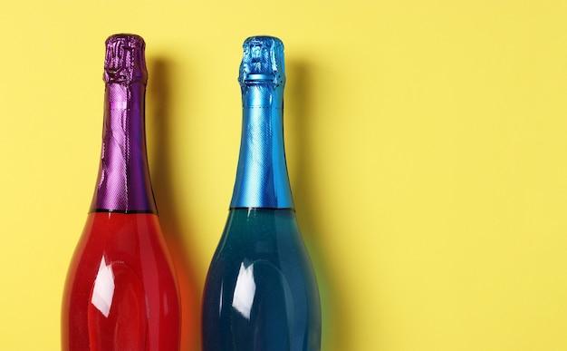 Shimmer eetbare glitter sprankelende roze en blauwe champagne in twee flessen op gele achtergrond. ruimte voor tekst.