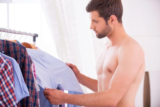 Shirt kiezen om te dragen. knappe jonge man die een wit overhemd verkleedt en naar de camera kijkt
