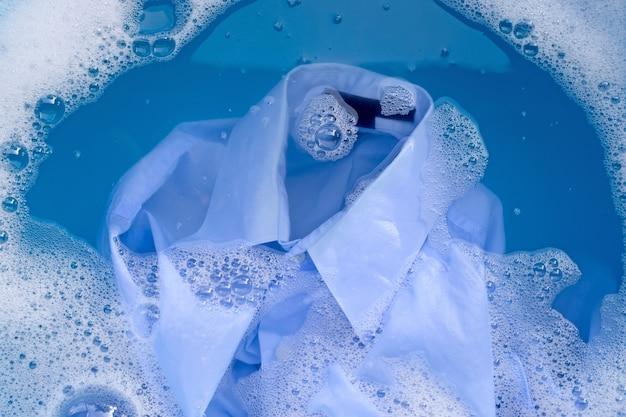 Shirt weken in poeder wasmiddel water oplossen, washandje. wasserij concept.