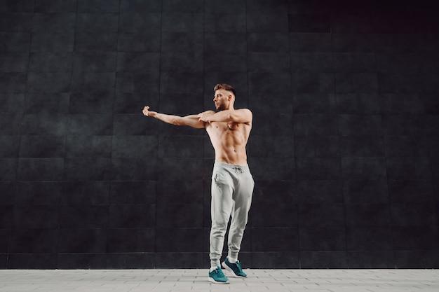 Shirtless aantrekkelijke gespierde blonde man doet warming-up oefeningen voor armen terwijl je voor donkere muur